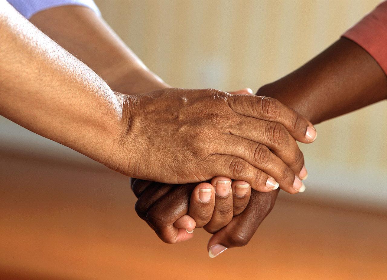 zwei schwarze Hände halten zusammen
