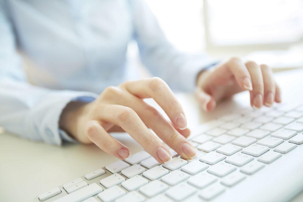 Eine Frau tippt mit beiden Händen auf einer weißen Computertastatur