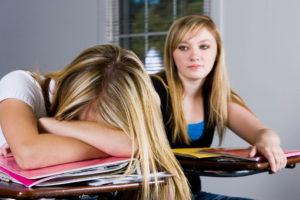 Schülerin schläft über den Heften im Unterricht