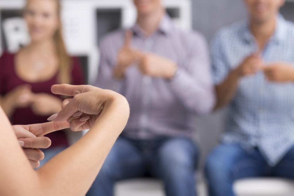 Frau kommuniziert in Gebärdensprache mit drei Personen