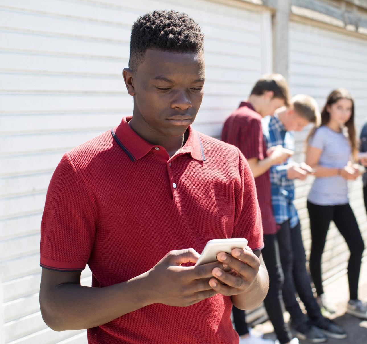 Abseits von der Gruppe; Jugendlciher blickt traurig auf sein Handy.