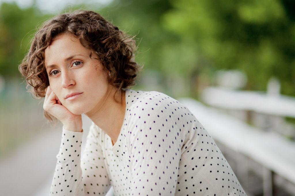 Frau sitzt auf einer Bank und schaut nachdenklich