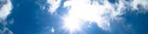 Die Sonne strahlt durch leicht wolkenverhangenen blauen Himmel