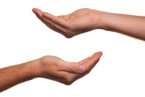 Zwei Hände übereinander mit einer bittende Geste